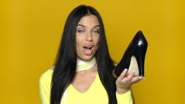 Sexy girl comparing shoes on yellow background — Stock Video #12770839