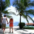 Romantic couple walking on bridge between palm trees - Stok fotoğraf