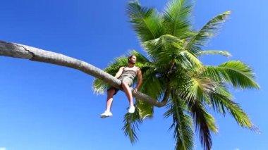 Bell'uomo è seduta su un albero di Palma — Video Stock