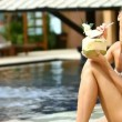 Beautiful girl sitting at the edge of swimming pool and drinking from coconut — Stock Video