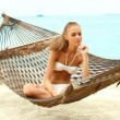 Beautiful smiling woman with long blonde hair sitting cross legged in a hammock — Stock Video #12815370