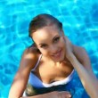 Beautiful young woman resting in the swimming pool on the sunny day — Stock Video