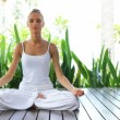 Woman in lotus position meditating - Stock Photo