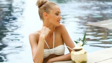 Adorable blond woman standing in swimming pool and drink from coconut — Stock Video