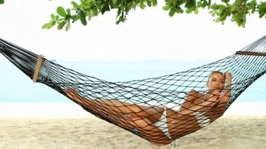Beautiful woman full of vitality reclining suntanning in a hammock — Stock Video