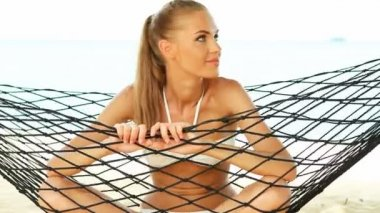 Beautiful smiling woman with long blonde hair sitting cross legged in a hammock — Stock Video