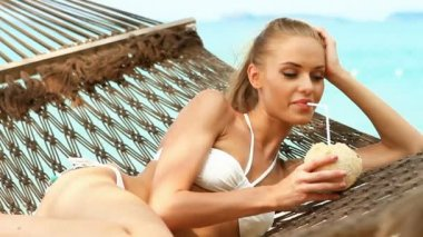 Adorable woman laying and drinking from coconut — Stock Video
