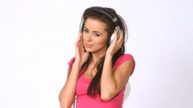 Close up of pretty girl which listen to the music in headphones