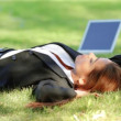 Beautiful business woman relaxing on grass with laptop - Stock Photo