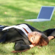 Beautiful business woman relaxing on grass with laptop — Stock Video #12893013