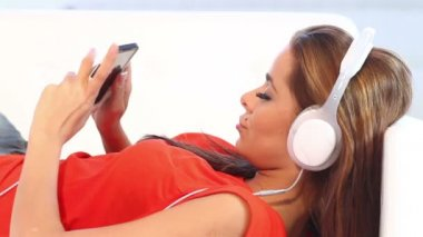 Jong meisje op bank luisteren naar de muziek met koptelefoon — Stockvideo