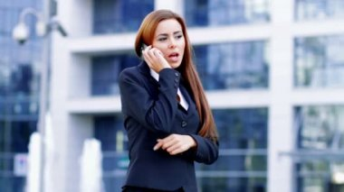 Adorable business woman using mobile phone outside office — Stock Video