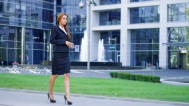 A beautiful business woman walking outside office building — Stock Video #12892827