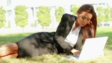 Beautiful business woman laying on grass and using laptop