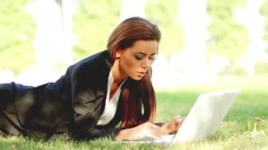 Beautiful business woman laying on grass and using laptop — Stock Video #12892971