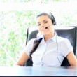 Beautiful young businesswoman talking phone with headset - Stock Photo