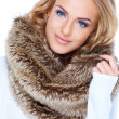 Gorgeous blond woman wearing fur scarf and smiling — Stock Photo #13738560