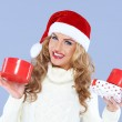 Smiling woman in Santa hat holding Christmas gifts — Stock Photo