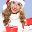 Close up of woman in Santa hat holding Christmas gifts — Stock Photo