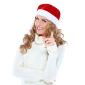 Young woman with a Santa hat pointing — Stock Photo