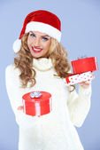 Pretty woman in Santa hat holding Christmas gifts — Stock Photo