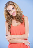 Confident young lady with folded arms smiling at the camera — Stock Photo