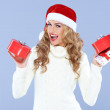 Sexy woman in Santa hat trying to decide which gift — Stock Photo