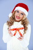 Close up of woman in Santa hat holding Christmas gift — Stock Photo