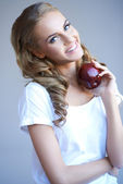 Head shot of woman holding red apple against grey — Stock Photo