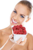Close up of smiling blonde holding raspberries — Stock Photo