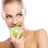 Woman tries to bite a fresh green apple — Stock Photo