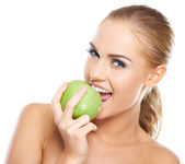 Beautiful young woman bites a green apple — Stock Photo
