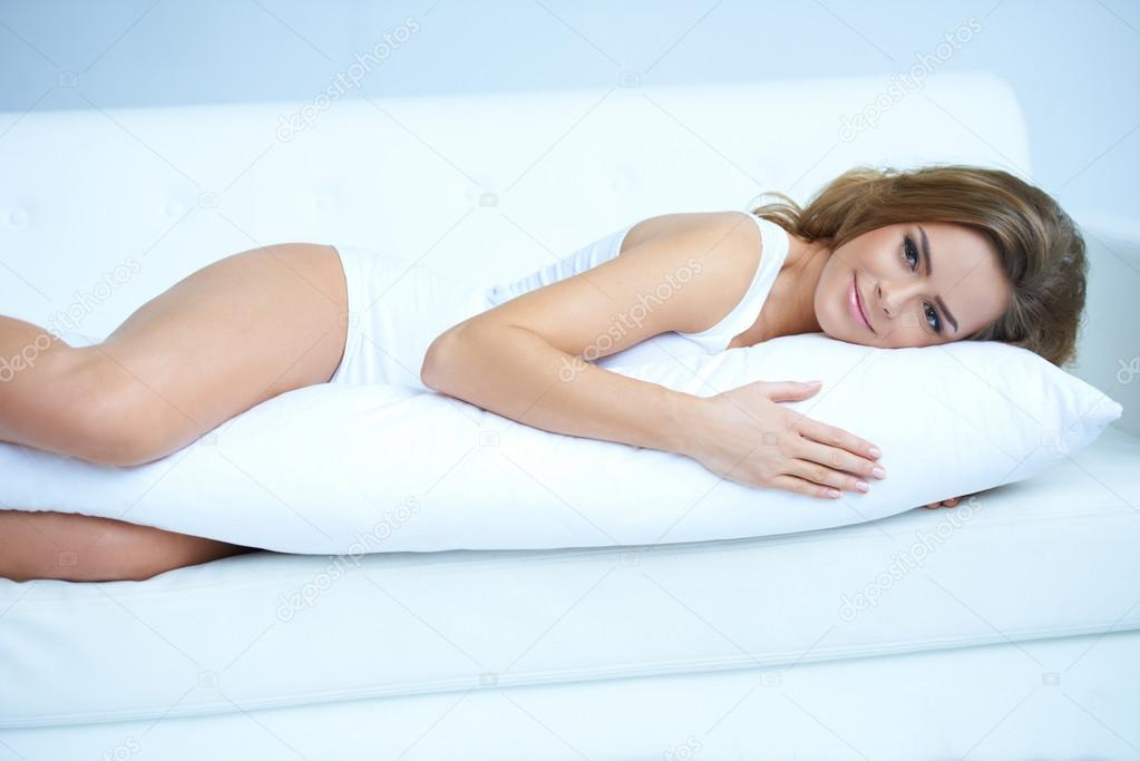 Young pregnant woman laying on white sofa   #14088900