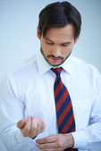 Attractive young man doing up his shirt cuffs — Stock Photo