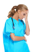 Doctor holding her head in anguish — Stock Photo