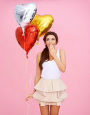 Cute woman with heart shaped party balloons — Stock Photo