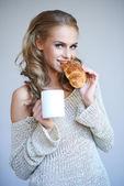 Mujer disfrutando de un fresco croissant crujiente — Foto de Stock