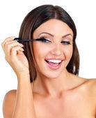 Mulher feliz aplicando rímel — Foto Stock