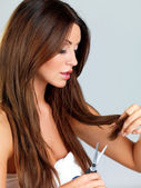 Woman trimming the ends of her long hair — Stock Photo