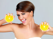 Playful woman with two orange halves — Stock Photo