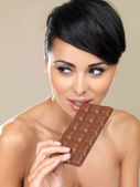 Beautiful woman with a bar of chocolate — Stock Photo