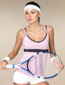 Attractive woman with a tennis racquet — Stock Photo