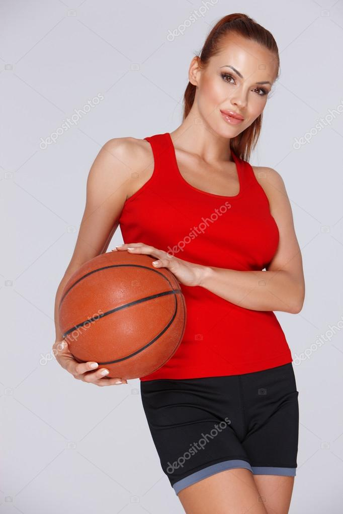 Low angle portrait of an attractive woman with a basketball in her hands posing in shorts against a grey studio background — Stock Photo #19182513