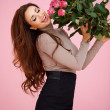 Stock Photo: Happy vivacious womwith pink roses