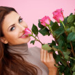 Stock Photo: Beautiful womsmelling rose