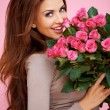 Laughing romantic woman with roses - Stock Photo