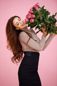 Happy vivacious woman with pink roses — Stock Photo