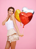 Vivacious woman with heart shaped balloons — Stock Photo