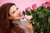 Güzel kadın bir gül kokulu — Stok fotoğraf