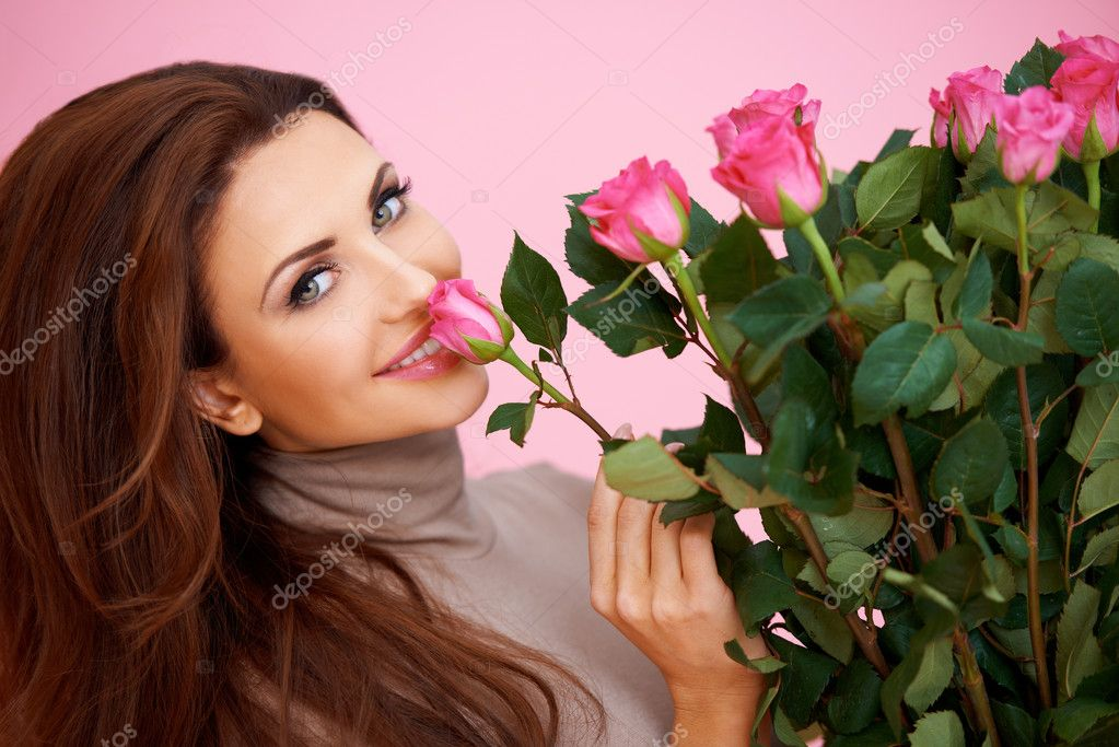 Beautiful woman with a large bouquet of flowers in her arms smelling a fragrant pink rose — Stock Photo #19207505